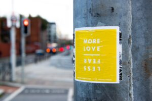 yellow flyer posted on post with words love more fear less