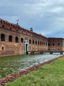 large brick structure in background with water surrounding it and grass in the lower side